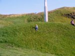 Lily playing on a hill while Daddy and Mummy have some coffee